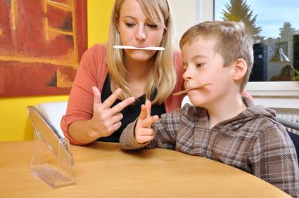 Eine Logopädin mit einem jungen Patienten