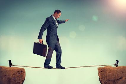 Mann auf einem gespannten Seil zwischen zwei Klippen