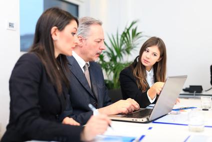 Zwei Frauen sitzen neben einem Mann am Rechner