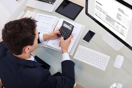 Steuerfachangestellter arbeitet mit Taschenrechner