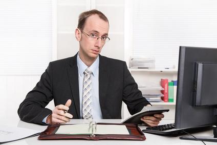Anspruch auf das Arbeitszeugnis: Skeptischer Geschäftsmann in Anzug und Krawatte