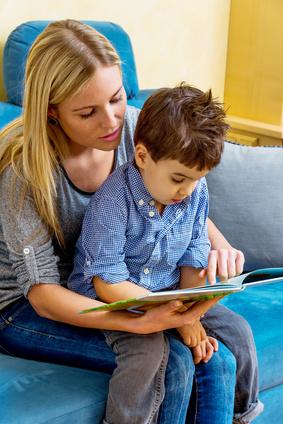 Frau liest Kind auf ihrem Schoß aus Buch vor