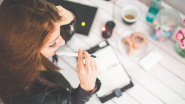 Das Fernstudium – Hochschulabschluss hausgemacht? Frau sitzt am Schreibtisch und arbeitet
