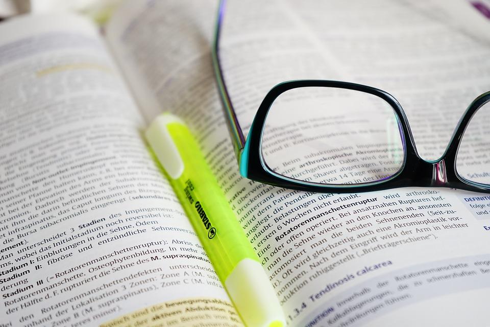 Offenes Buch mit Brille und Textmarker