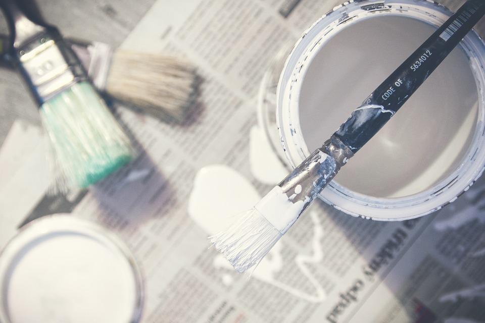 Pinsel und Farbeimer auf Zeitung