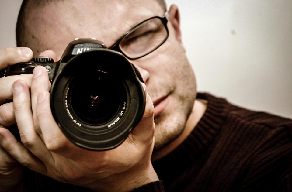 Fotograf mit Kamera vor dem Gesicht