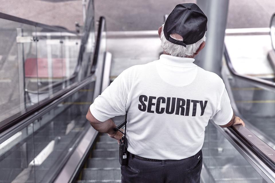 Security Mann auf einer Kaufhaus Rolltreppe